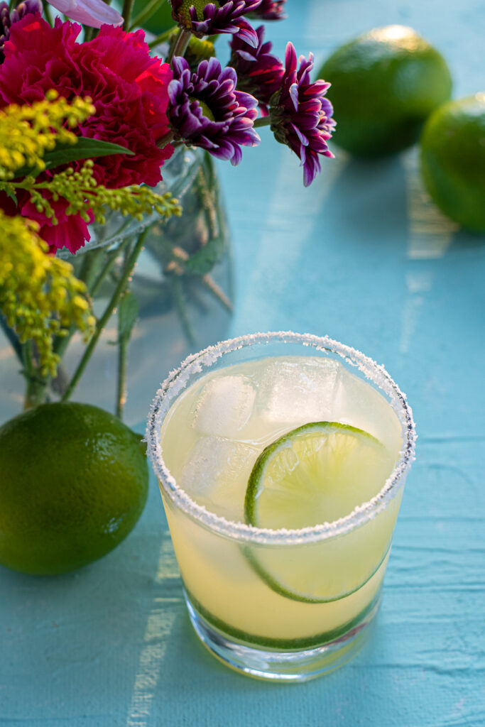 A salt rimmed glass filled to the top with ice and margarita, topped with a lime wheel.