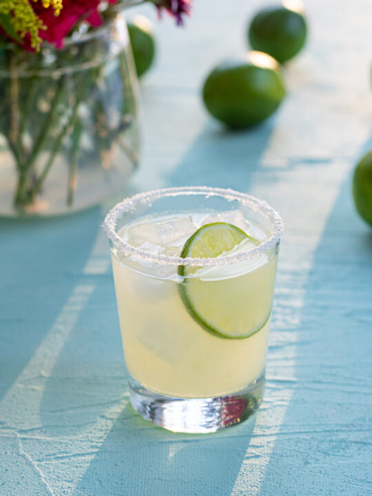 A glass with a salt rim filled with classic margarita cocktail and ice, topped with a lime wheel, in the background limes and flowers.